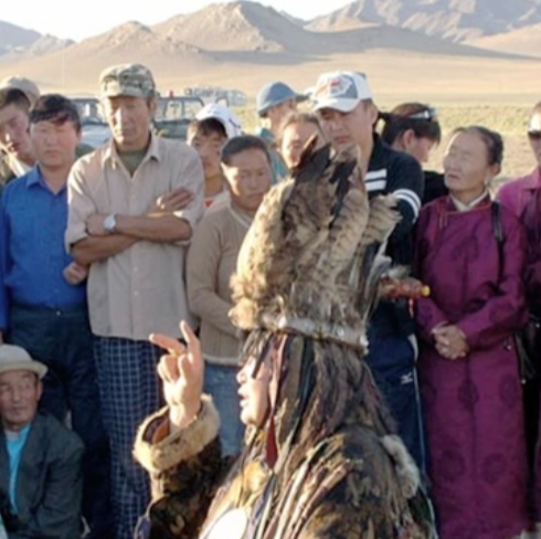 Mongolian shaman explaining solar eclipse measures to a crowd of Mongolians.