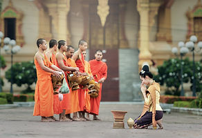 Canva - Woman Praying in front of Monks.