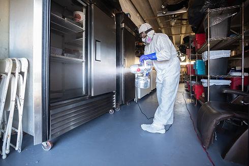 Worker disinfecting an industrial kitchen freezer