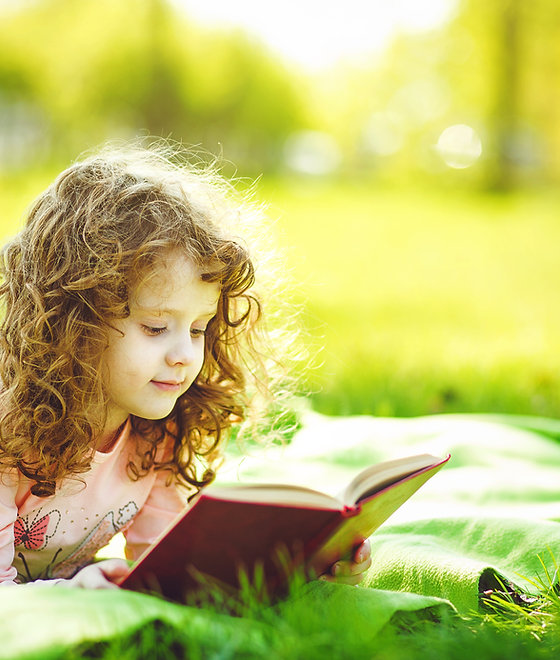Little girl reading a book in the spring park, toning photo.jpg