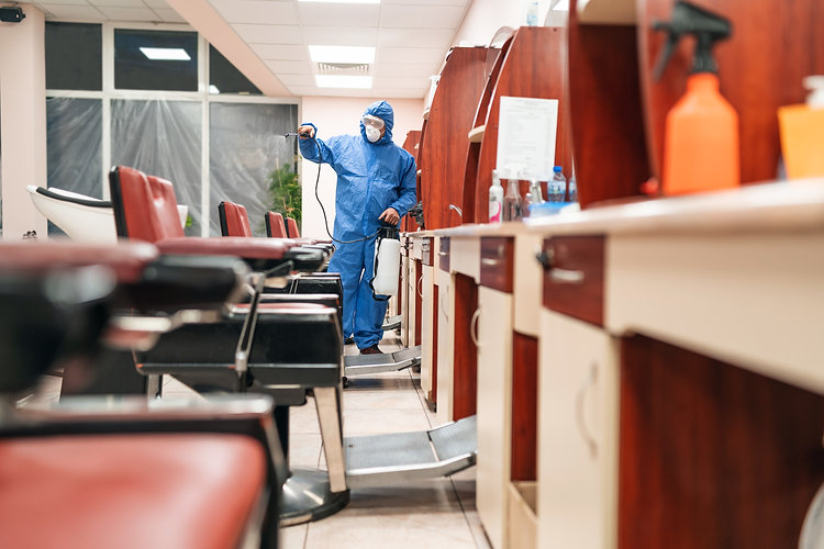 Frontline Worker with protective suit disinfecting hairdressing studio with chemicals