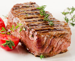 Beef Steak With Fresh Herbs On A  White Plate .