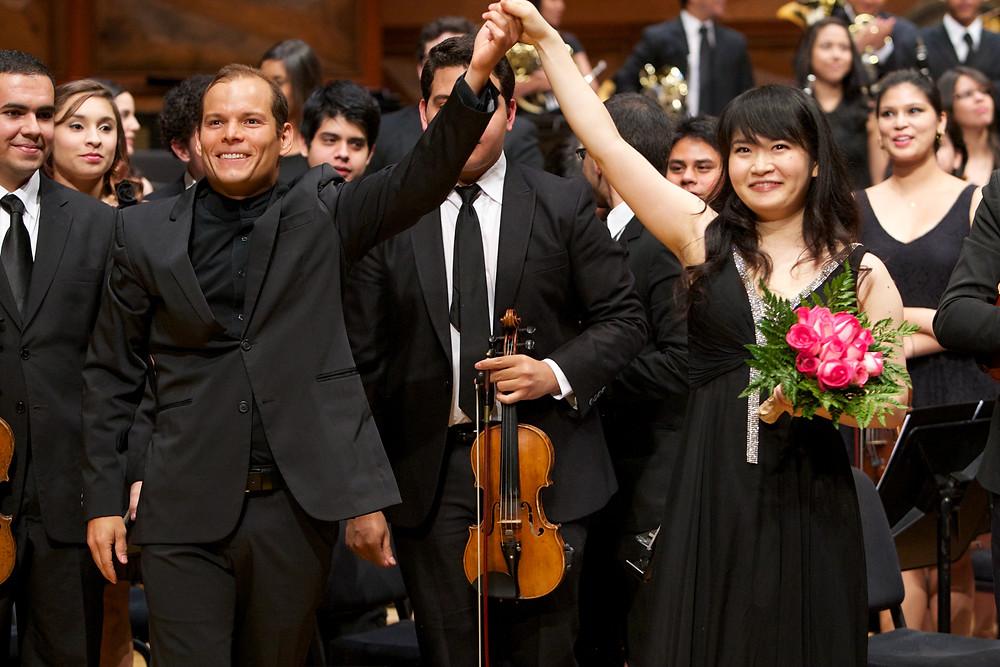 2013年6月、カラカスのシモン・ボリバル・ホールにて。EYOCとの演奏を終え、指揮者のディートリヒ・バレーデス氏と笑顔で手をつなぐ萩原さん。