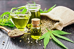 Hemp oil in two glass jars and sauceboat
