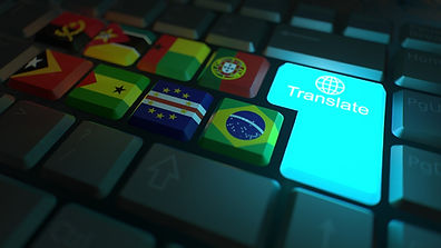 """Monitor de um computador, na tela, a foto de um teclado com a palavra """"translate"""" ou seja """"tradução"""" em português. A sua esquerda estão as bandeiras da Angola, Moçambique, Guiné-Bissau, Portugal. A baixo, estão as bandeiras de Timor Leste, São Tomé e Príncipe, Cabo Verde e Brasil"""""""
