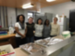 5 students gather around the kitchen after completing a service project.