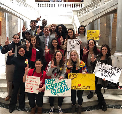Several students at the Kentucky State Capitol participating in Cards in Action. Some hold signs and hold their hands up to form the letter L.