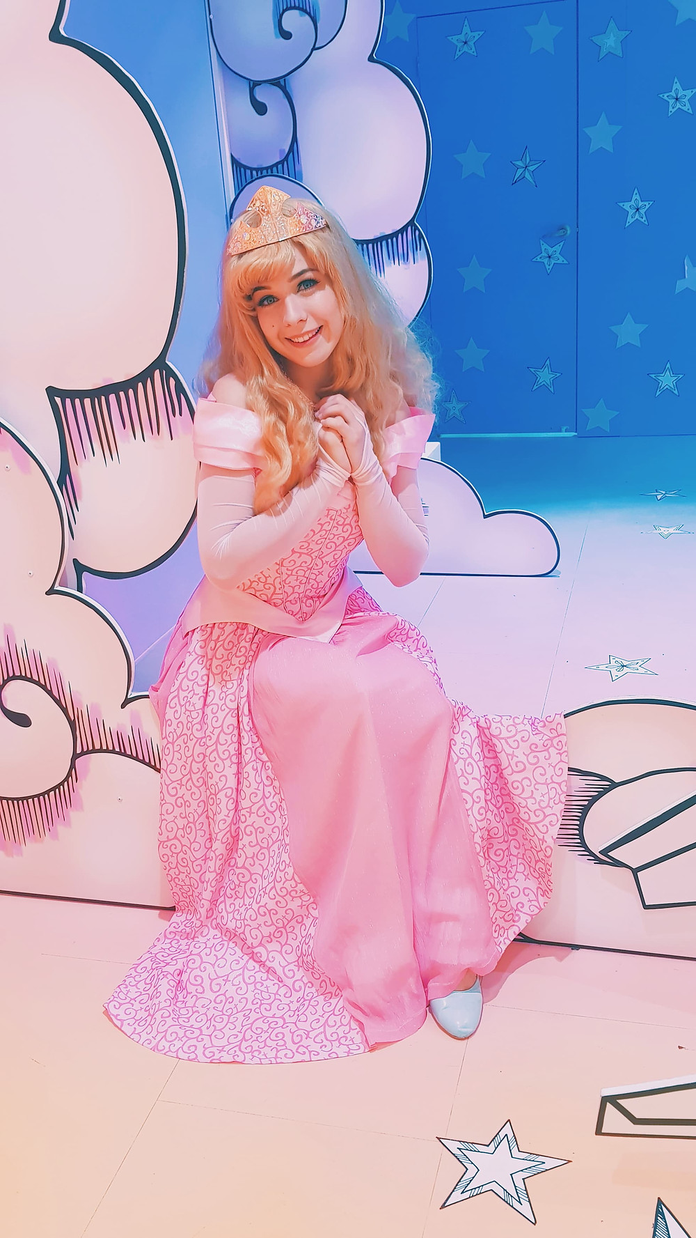 Princess Aurora sitting on a cloud in her pink dress