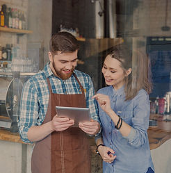Smiling handsome waiter holding tablet and young pretty woman pointing on it in coffee sho