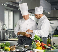 Two Famous Chefs Discuss Their Video Blog while Using Tablet Computer. They Work on a Big