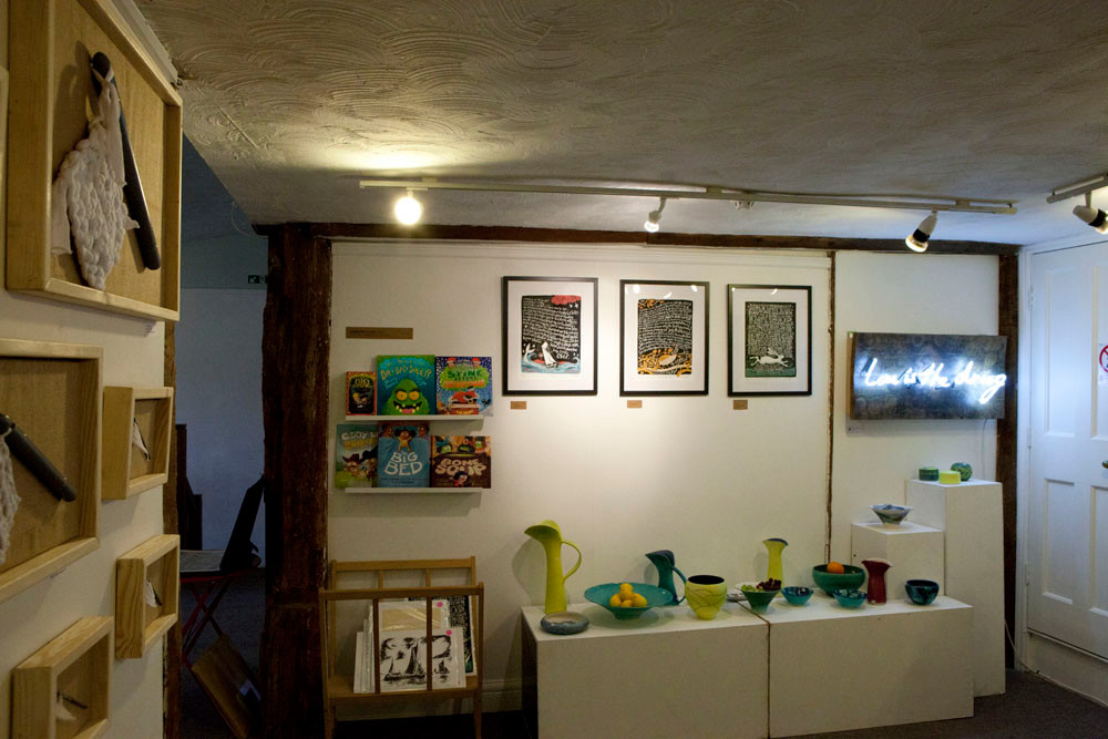 From right to left you have the work of the textile artist Clare Sams, alonside the books and prints by the illustrator Tom Knight, below which is the bright porcelain work of the ceramisit Usch Spettigue and finally the neon sign by Matt Mackman
