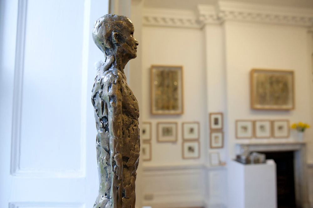 One of John O'Connors figurative sculptures overlooks the comings and goings in the Ballroom with the work of Nicola Coe in the background.