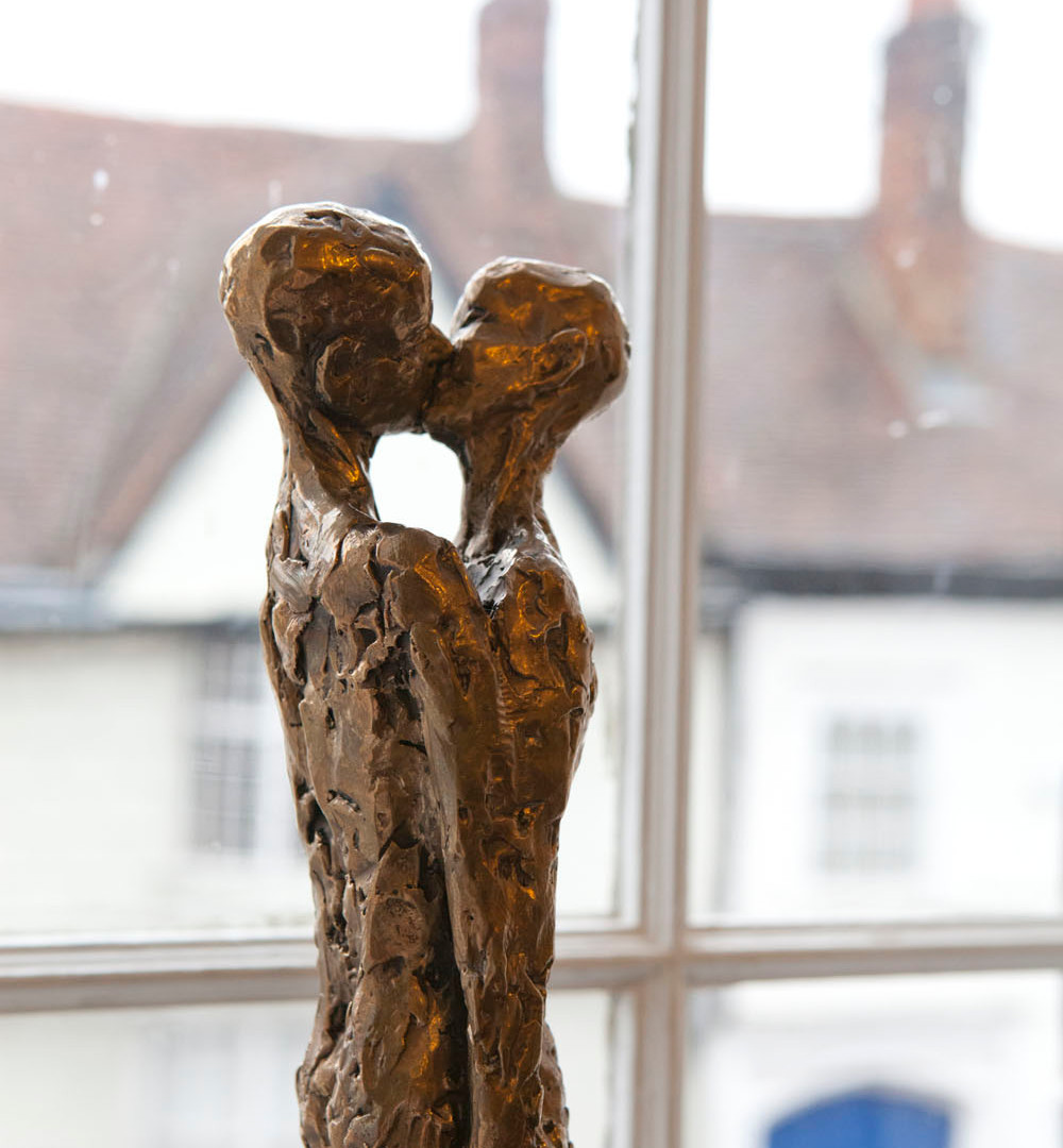"John O'Connors bronze sculpture ""Kiss"" displayed next to the window as part of the art fair."