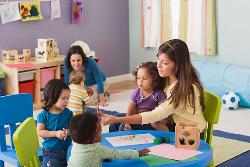Preschool teachers working with infants and toddlers at a childcare center.
