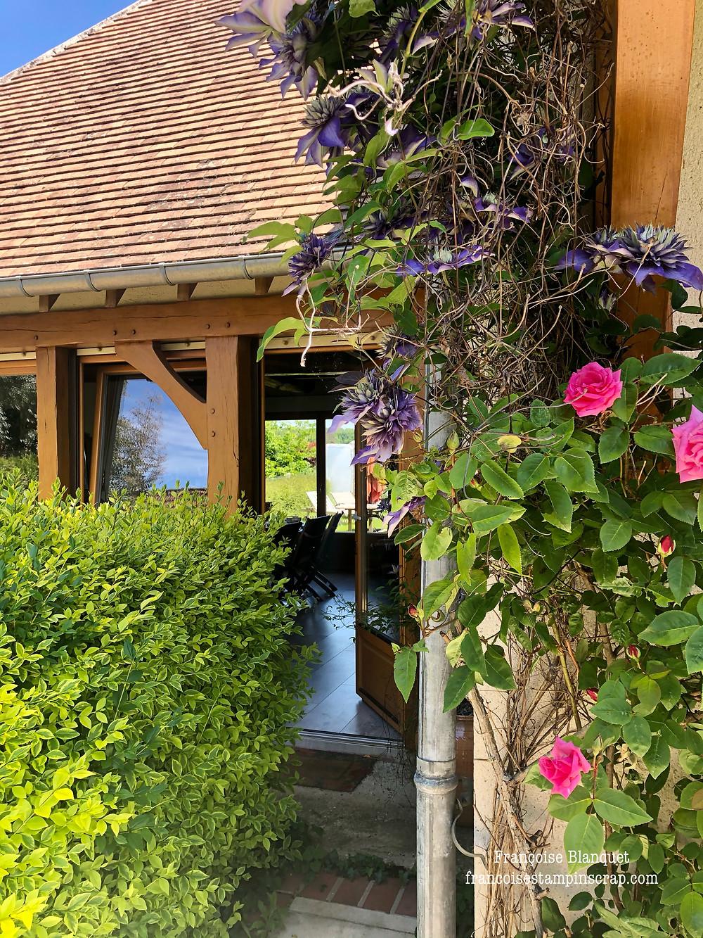 Une clématite Multiblue vous accueille avec générosité !  Le rosier embaume de son parfum, la saison est juste géniale.  On pousse la porte de mon atelier ....  Bienvenue chez moi !!  Bienvenue dans le monde du scrap