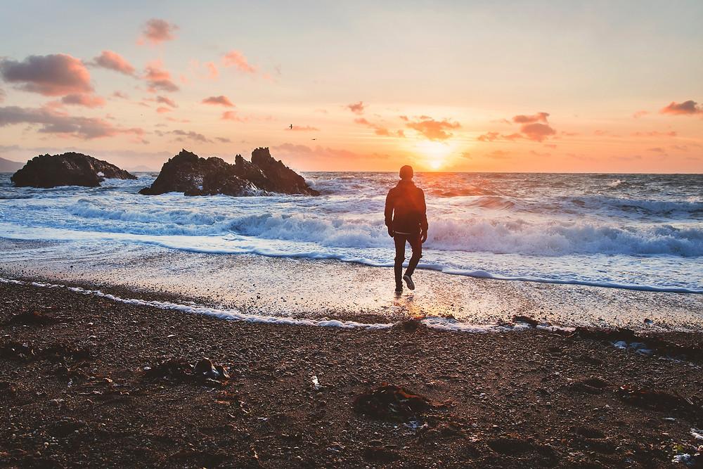 Man on the beach looking into the sun.