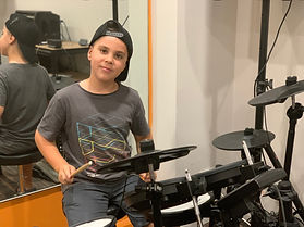 Boy playing drumkit.