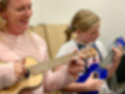 Happy mum and daughter playing ukulele