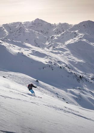 Skifahrer im Tiefschnee bei Sonnenuntergang