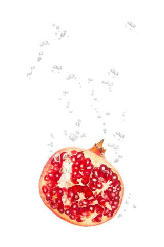 Granatapfel im Wasser mit Luftblasen