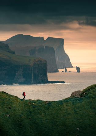 Mann wandert auf Klippe auf der Insel Kalsoy im Sonnenuntergang