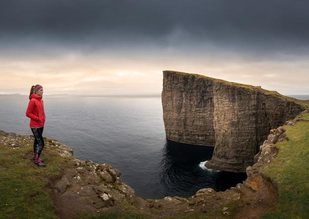 Panorama mit Frau an Klippen bei Trælanípa, Färöer Inseln