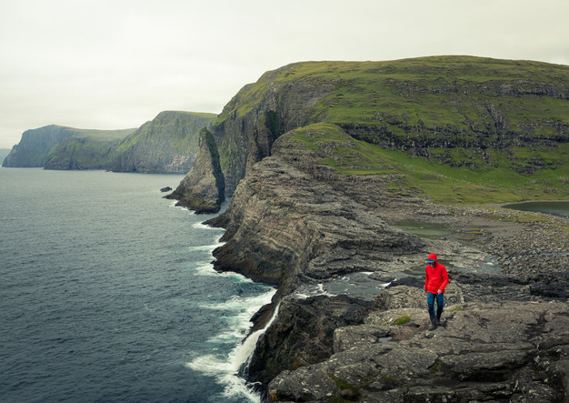 Mann in roter Jacke an Küste von Vagar, Färöer Inseln