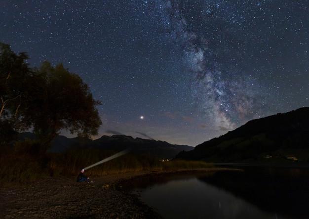Mann mit Stirnlampe unter Milchstrasse am Nachthimmel