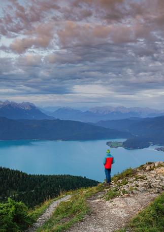 Person am Jochberg mit Blick auf Walchensee