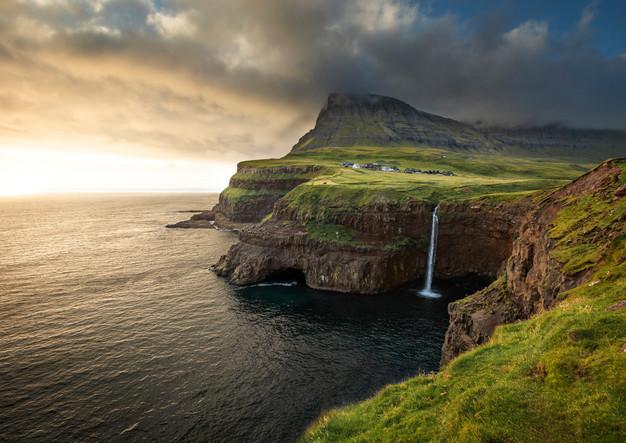 Sonnenuntergang am Wasserfall Múlafossur mit Dorf Gásadalur, Färöer Inseln