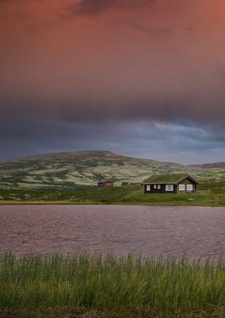 Norwegische Hütten am See im Sonnenuntergang