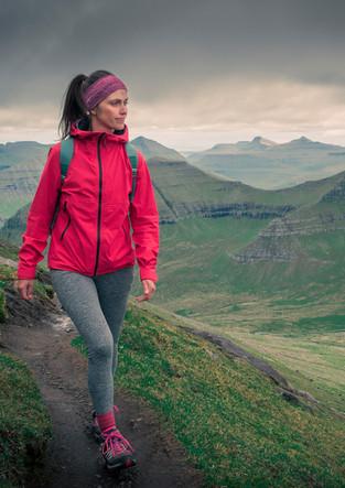 Frau wandert in Berglandschaft auf Eysteroy, Färöer Inseln