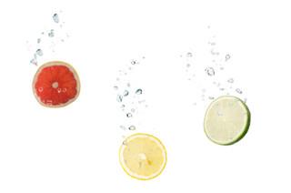 Grapefruit, Zitrone und Limone im Wasser mit Luftblasen
