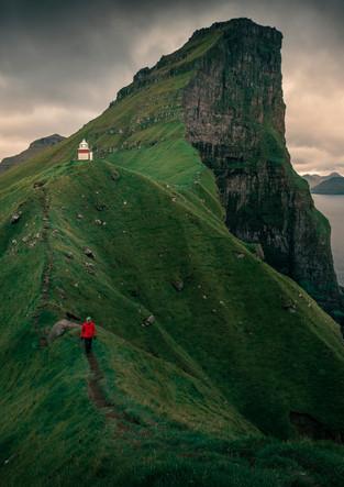 Mann auf Grat am Leuchtturm Kalsoy, Färöer Inseln