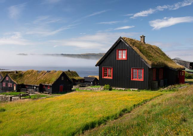 Häuser mit roten Fenstern und Grasdach im Dorf Kirkjubøur