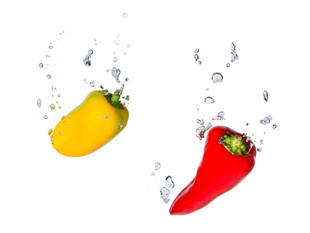 Red and yellow peppers in the water with air bubbles