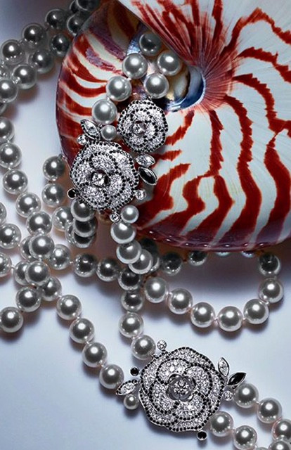Chanel pearl necklace with jeweled camellias over shell