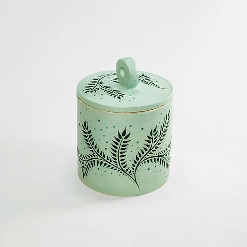 Front view of cylindrical jar with flat lid and circular handle. Painted in light green with dark green glaze fern decoration