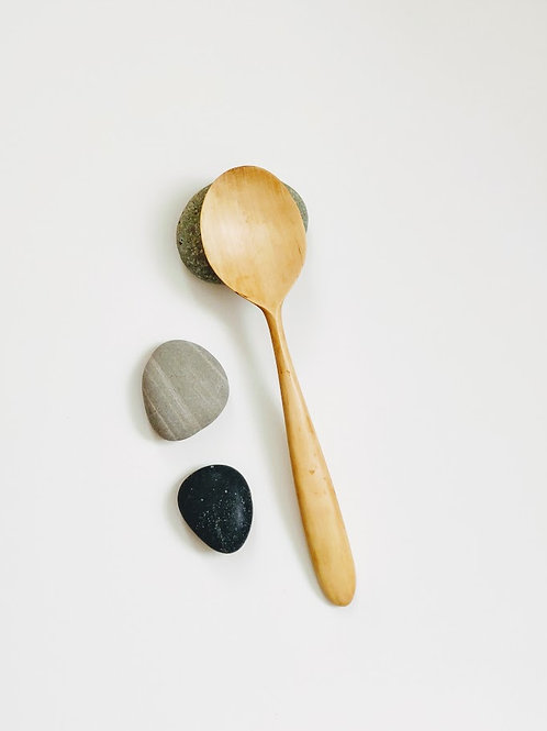 Front view of simple, elegant spoon with drop-shaped head and long rounded handle. Pale grain.