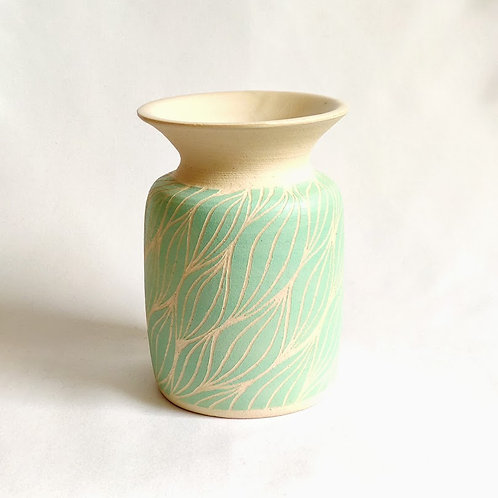 Small vase with light green botanical repeated motif carved against off-white background.