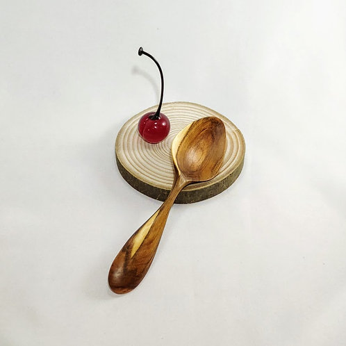 Front view of spoon, shown with glass cherry for scale.