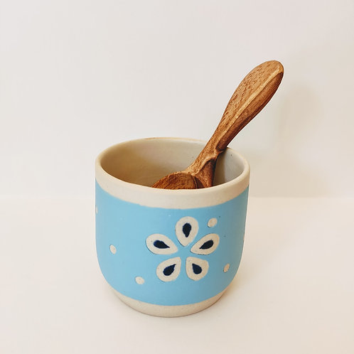Small white stoneware pot with a light blue background, flower-shaped carved decoration inlaid with painted glaze.