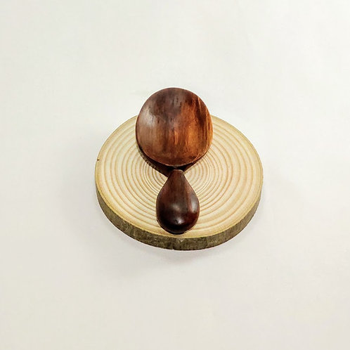 Top view of small oval scoop with rounded handle. Dark burnished wood grain.