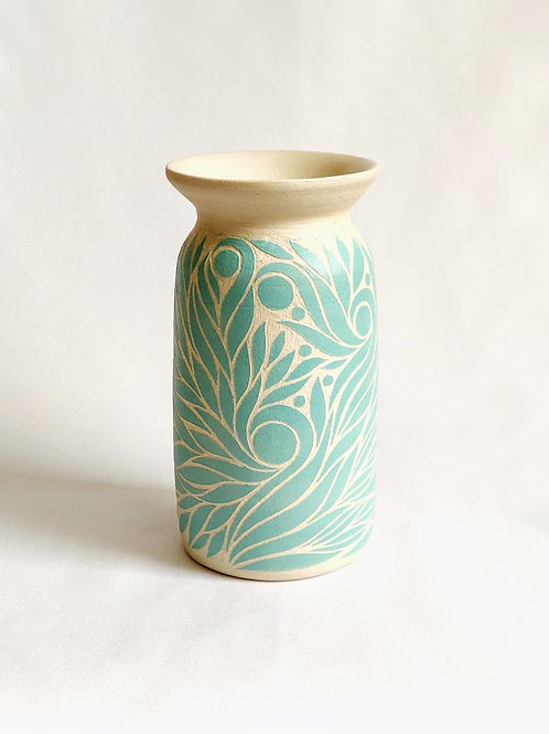 Small vase with light blue-green botanical pattern carved against off-white background.