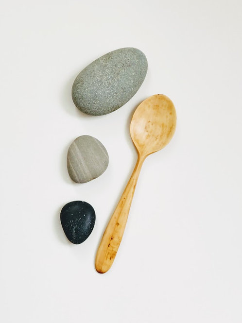 Front view of simple spoon with large head and flat handle tapered towards the top.