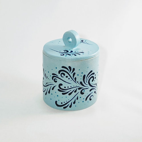 Front view of cylindrical jar with flat lid and circular handle. Cobalt glaze swirl design against light blue background.
