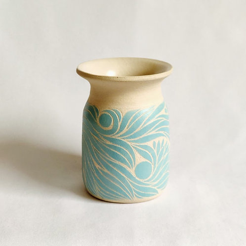 Small vase with light blue botanic motif carved against an off-white background.
