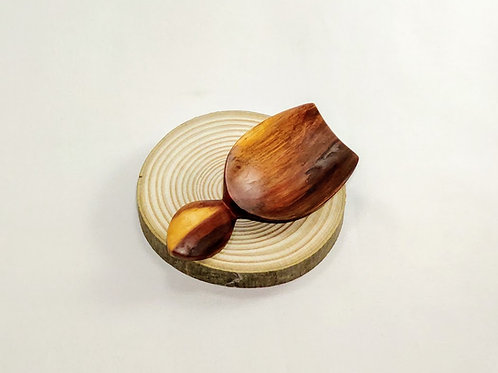 Front view of small scoop with a straight edge, and flat leaf-shaped handle. Dark burnished wood grain.