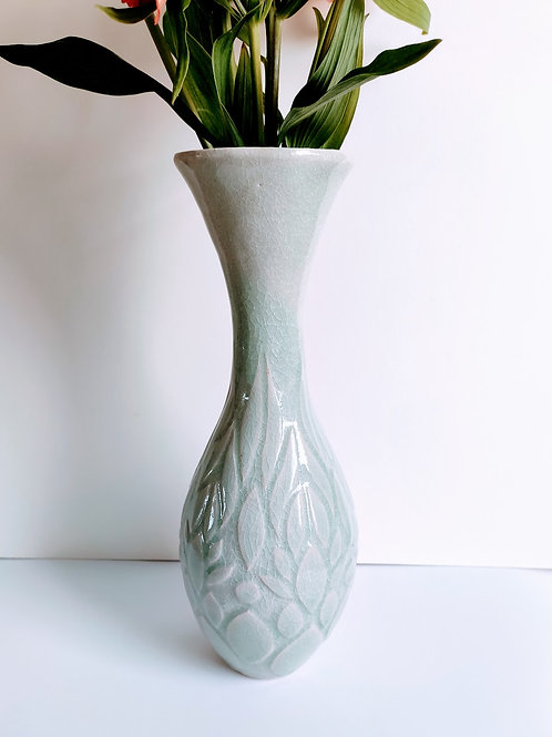 Slim vase with a tall neck flared at the top. Botanical relief pattern, with pale blue crackle-effect glaze.