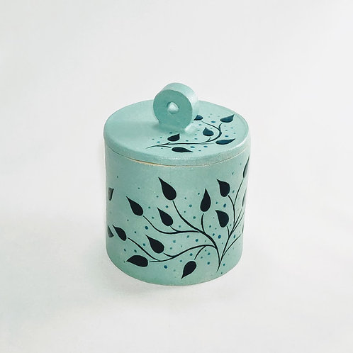 Front view of cylindrical jar with flat lid and circular handle. Botanical glaze decoration against blue-green background.